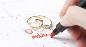 Wedding rings and hand writing word wedding into calendar