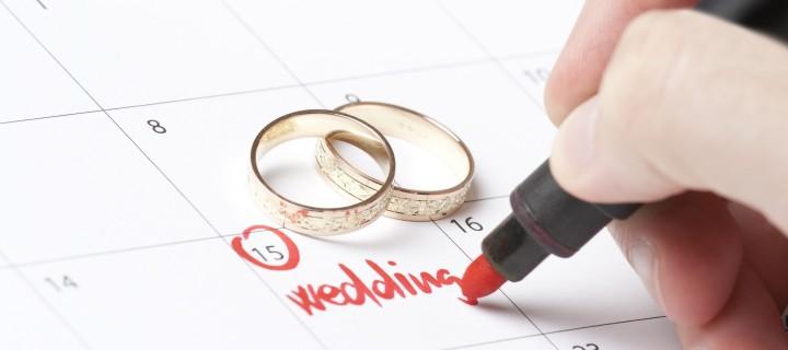 Wedding rings and hand writing word wedding into calendar